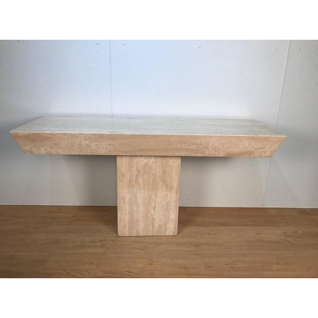 Italian modern monolith travertine console, with book-matched beautifully variegated stone rectangular stone top on a...