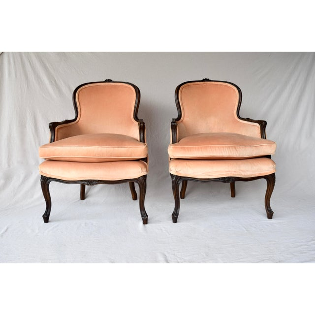 A pair of early 20th century hand-carved Bergere Chairs made in the Louis XV style. Original finish features salmon velvet...