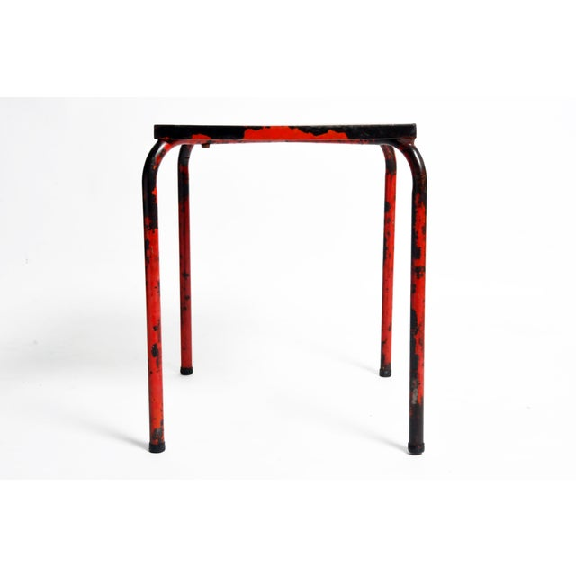This rustic red metal table is from France and was made, circa 1960. This brightly painted cafe table has an artistically...
