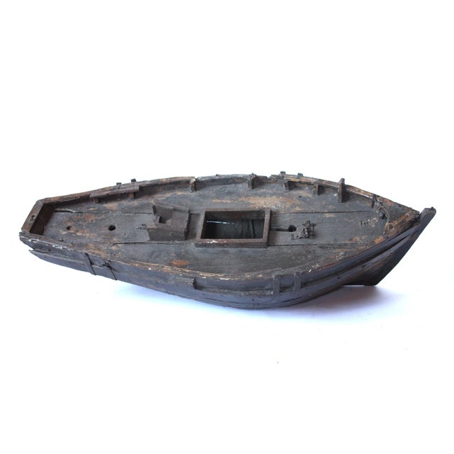 A large decorative wooden boat from England that has worn with time. A great display piece for a library or den.