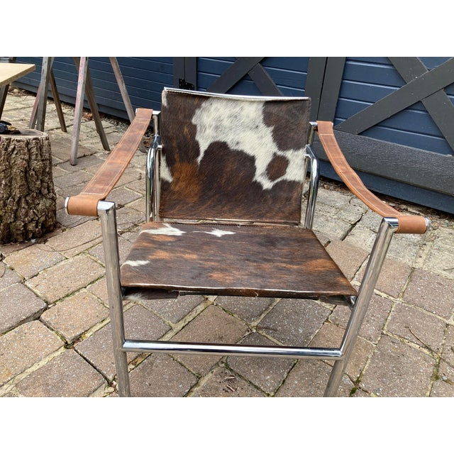 A vintage Le Corbusier LC1 style pony hide and Crome armchair.with leather arm rests and adjustable back