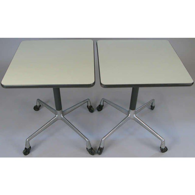 a matched pair of occasional tables from Eames Aluminum Group for Herman Miller. Four leg bases with casters, and laminate...