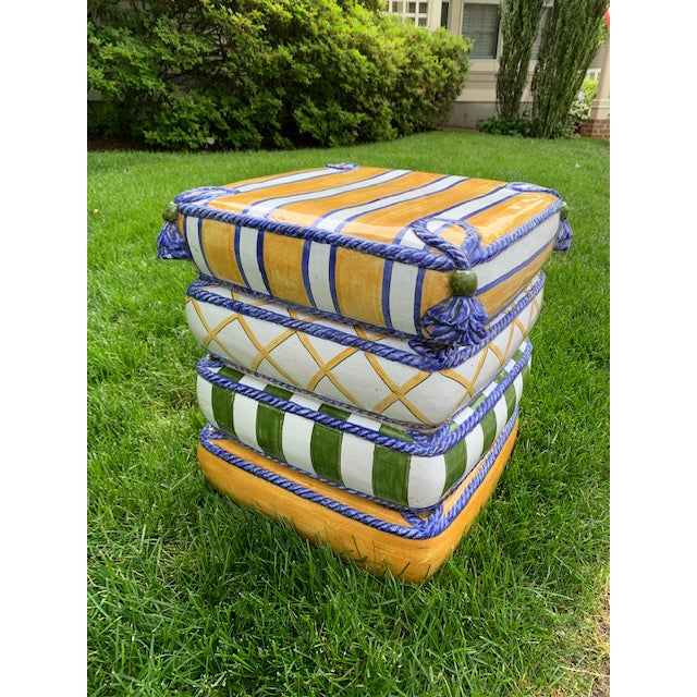 Vintage painted terra-cotta garden seat/side table. 4 Stacked Pillows with different patterns edged in a blue cord and...
