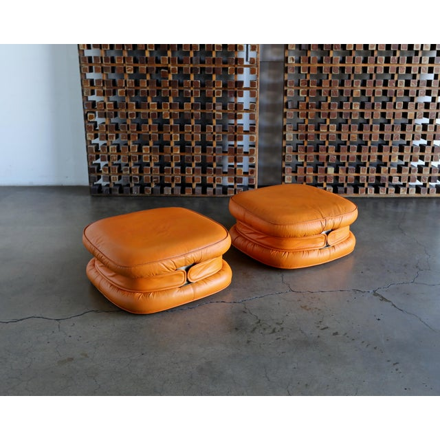 Offered is a pair of i4 Mariani leather ottomans, circa 1975. Upholstered in leather.