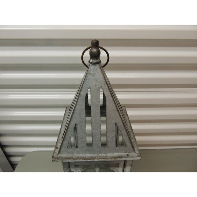 """Tall coastal weathered lantern. Hanging hood, tin roof and glass panels. Front door opens. Size: 25.1/4"""" H x 7.3/4"""" sq."""