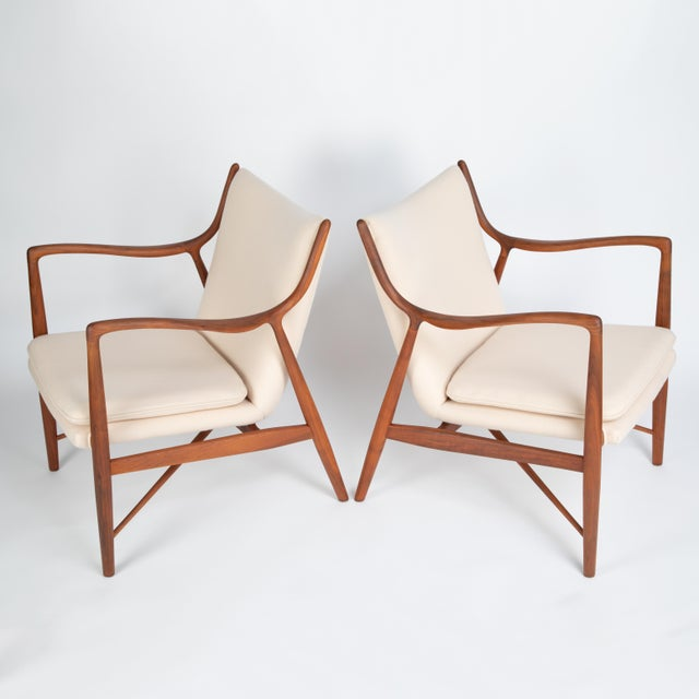 """Exquisite pair of Finn Juhl """"45"""" chairs with sculptural walnut frames supporting upholstered seats and backs with loose..."""