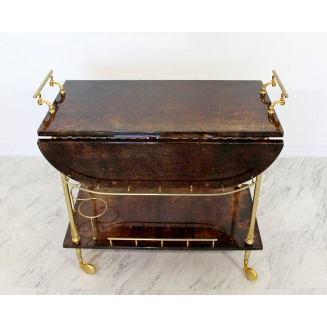 For your consideration is an absolutely stunning, brown goatskin lacquered bar cart, with brass accents, circa the 1950s....