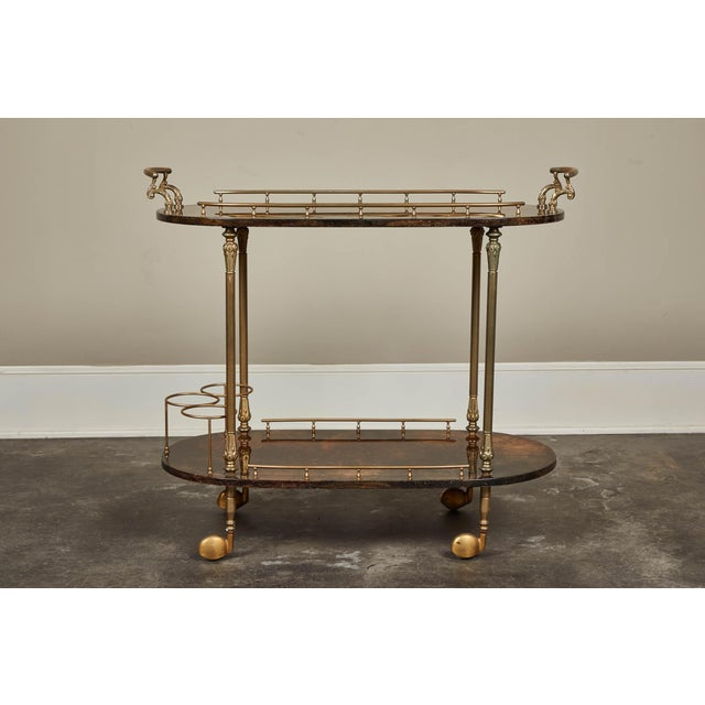 1950's Aldo Tura barcart in parchment and brass. Working wheels and two levels for cocktail service and storage. Brass...
