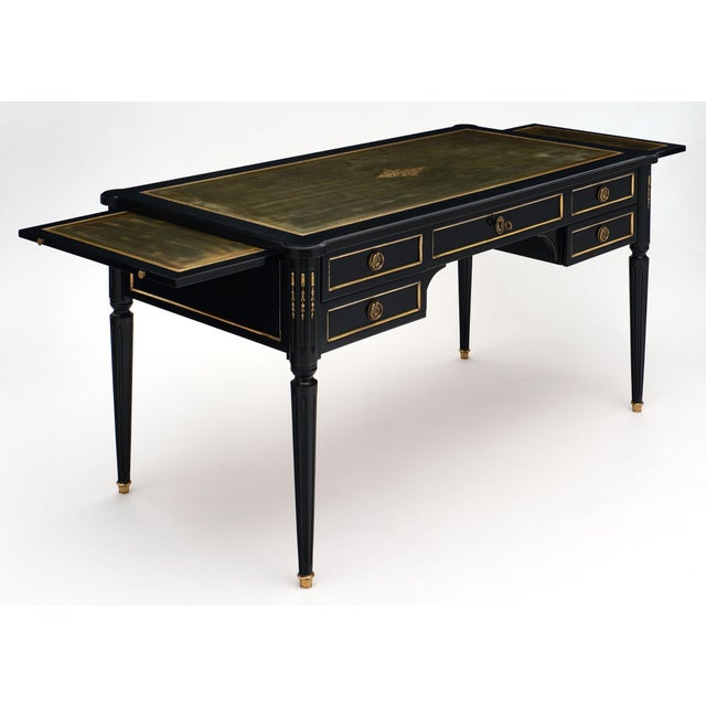 Antique French Louis XVI style writing desk enhanced with gilt brass hardware, tapered legs with bronze feet, and a...