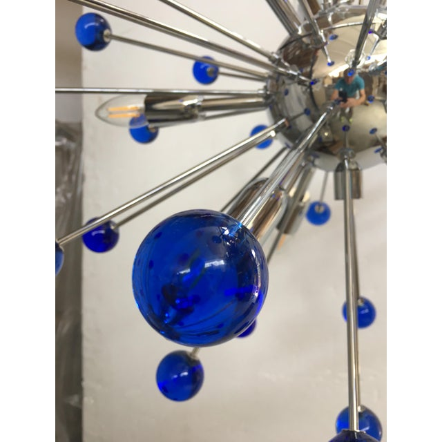 "Chandelier with a chrome base and round Murano glass balls in a royal blue color. The fixture is in the classic ""Sputnik""..."