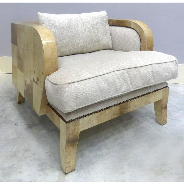 A comfortable pair of Art Deco club chairs covered in lacquered goatskin. Nicely upholstered in an off-white textured...