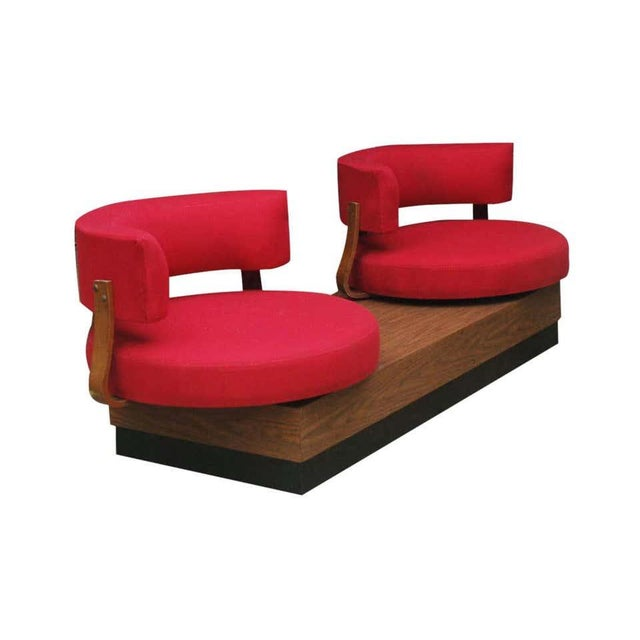An unusual design from the 1970s. It features a platform base with swiveling barrel back lounge chairs in red upholstery.