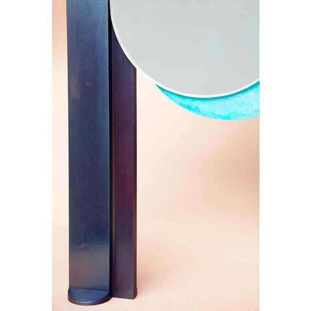 A pair of offset tempered steel arches frame two eclipsing mirrors, shifting to reveal textured patina plates. Like two...