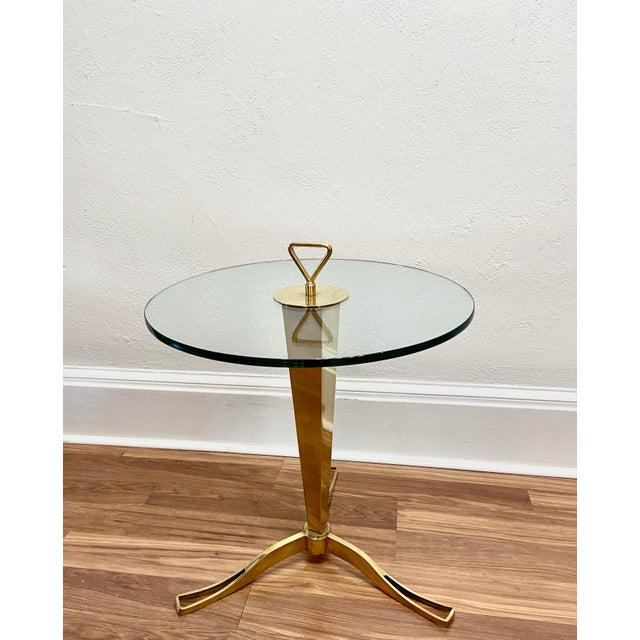 Polished brass faceted structure with 3-pronged foot and stylized finial or handle. Thick, circular crystal glass table...