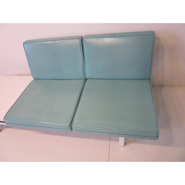 A two cushion turquoise colored leatherette sofa with a built in side table having a Formica top. Sitting on a white...