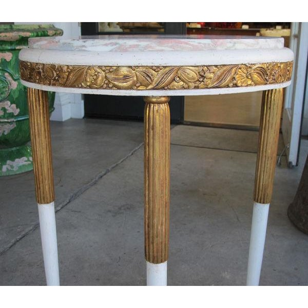 A chic French art deco gessoed and parcel-gilt circular side table with Norwegian-rose marble top; the subtly-figured...