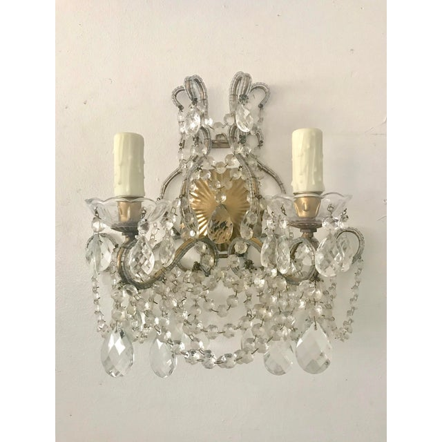 Gorgeous pair of two light gilt iron and crystal beaded sconces in the Italian style. The sconces are loaded with crystal...