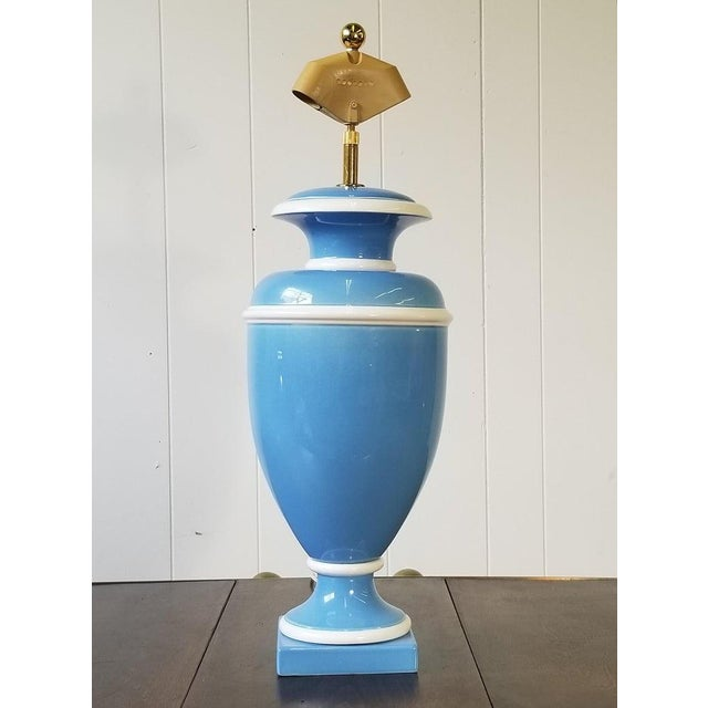 Dramatic Hollywood Regency Italian ceramic urn lamp in Wedgwood blue and trimmed in white. There is a built in and...