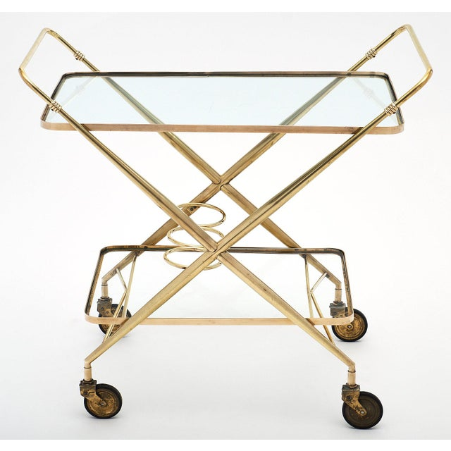 French vintage brass bar cart on casters with two glass shelves and three bottle holders on the bottom shelf. The x-shape...