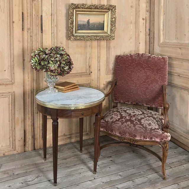 19th Century French Directoire Marble Top Round End Table was hand-crafted from solid imported mahogany, then fitted with...