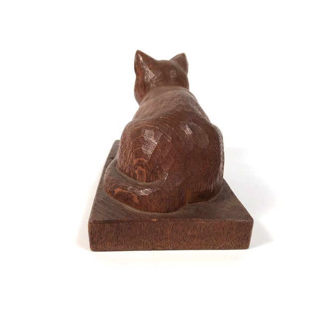 A beautifully hand carved wood folk art sculpture of a cat, in oak, resting, with alert expression, on a rectangular...