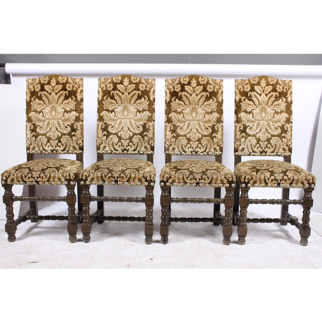 English Country House-style dining chairs featuring green and cream damask upholstery with brass nail heads and Tudor...