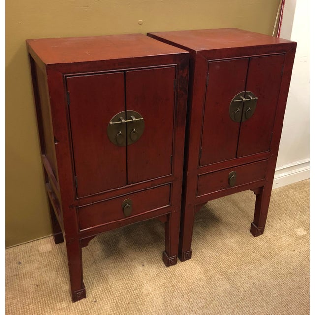 Pair of antique19th century Chinese red lacquer cabinets with brass hardware. Double doors with metal closure above a...