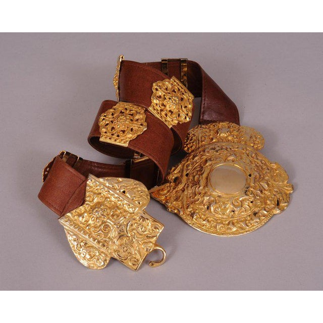 This supple brown leather belt is embellished with a large gold toned buckle and seven decorative slides in two different...