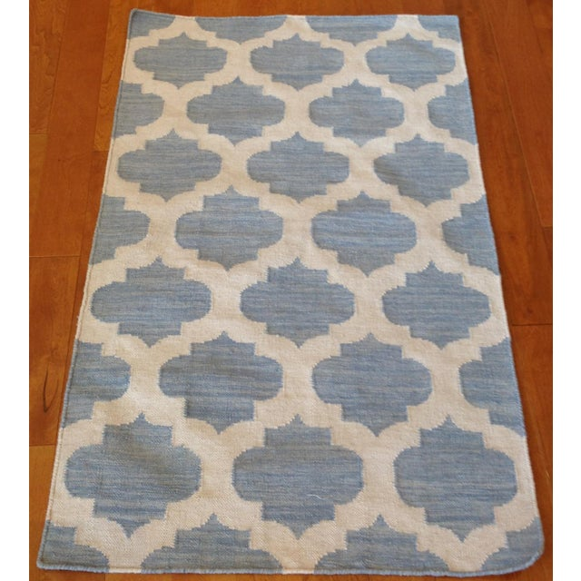 This light blue and beige, reversible, wool trellis kilim was hand-knotted in India.