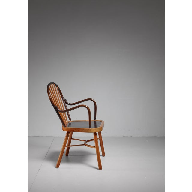 A wooden chair with a spindle backrest. The chair is built up from a very well selected combination of ash in different...