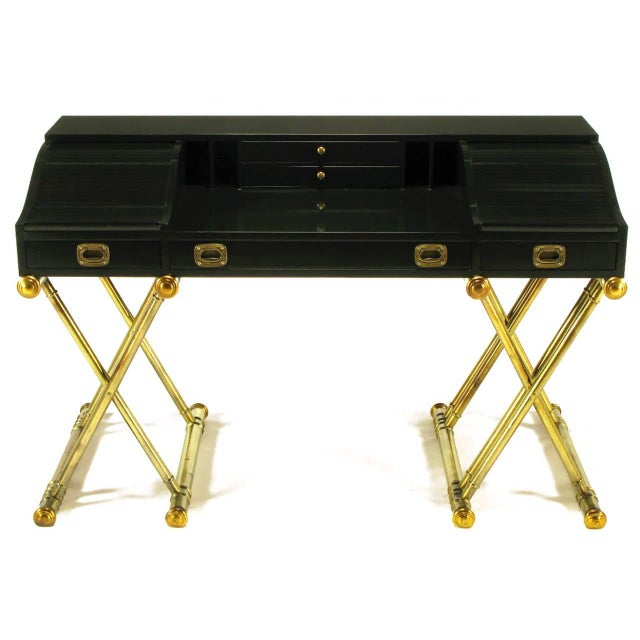 Handsome Campaign style desk! Featuring low roll tops or tambour doors on each side of the desk top which sits on a gilded...