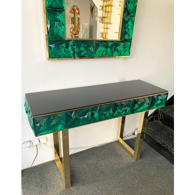 Contemporary wall mirror and console set, full brass and large pieces of green emerald Murano glass with relief diamond...