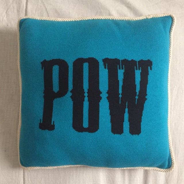 """Pair of turquoise & black pillows with white cording and """"POW"""" woven in a western style font on the front of each in thick..."""