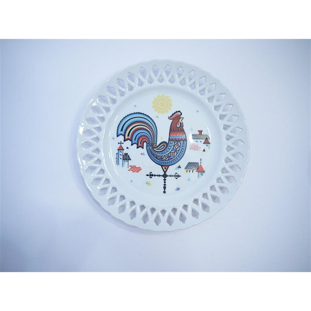 This whimsical reticulated plate depicts a rooster sat atop a weathervane with the sun and village in the background. The...
