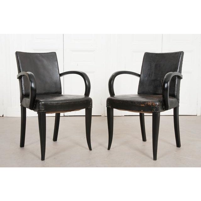 A stylish pair of ebony Art Deco period armchairs from 1930s France. The chairs have a somewhat simple form, with awesome,...
