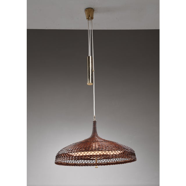 A mid-century height-adjustable pendant lamp made of a woven rattan shade with a curved plexiglass diffuser inside. This...