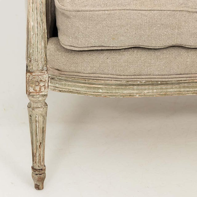 A lovely French Marquise loveseat circa 1850s. Newly reupholstered in linen with a painted carved frame in the Louis XVI...