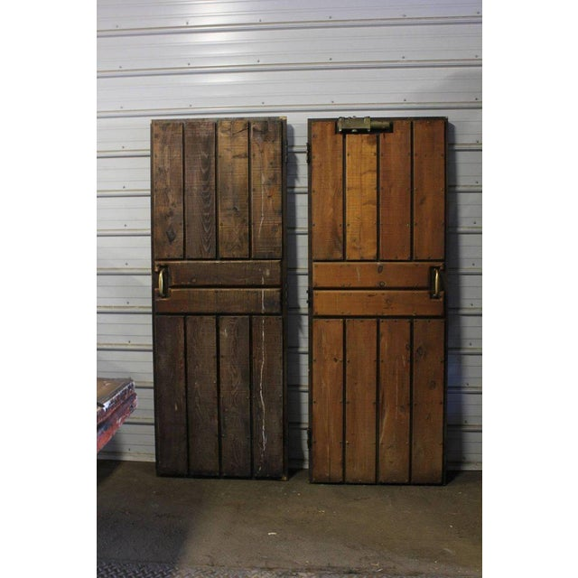 Vintage ship wooden doors with brass hardware and hand-carved signs men and women.