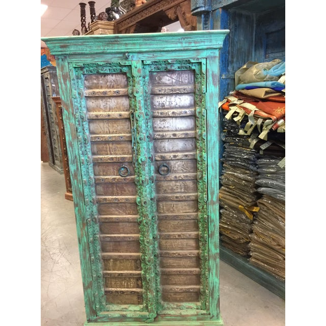 Vintage Cabinet Brass cladded doors from Jaipur India, hand hammered 18c old reclaimed haveli doors, open onto a large two...