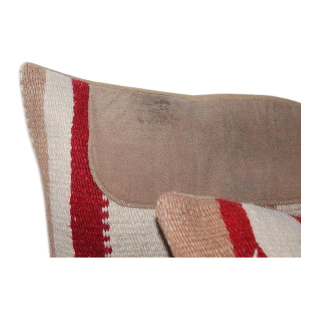 This pair of Navajo Indian weaving saddle blanket pillows with leather trim. They both have tan cotton linen backings.