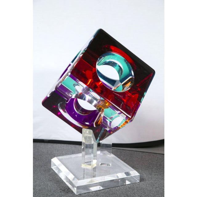 Hollow colored acrylic cube sculpture on original acrylic base. The cube measures 12 X 12 X 12. On its stand it measures...