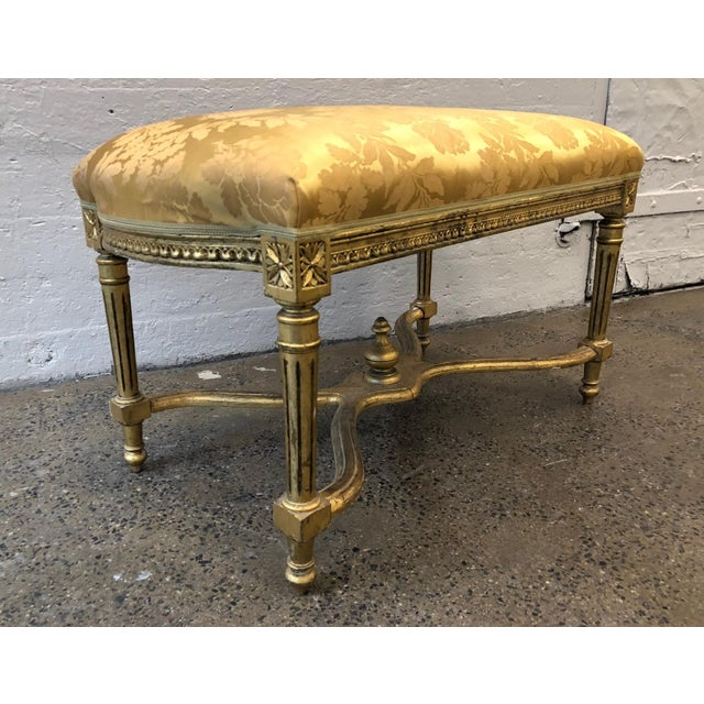 Louis XIV style giltwood bench. Upholstered in vintage gold silk fabric.
