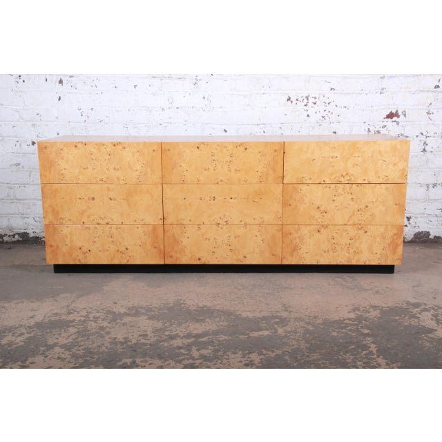 An exceptional mid-century modern burled olive wood long dresser or credenza designed by Milo Baughman. The dresser...