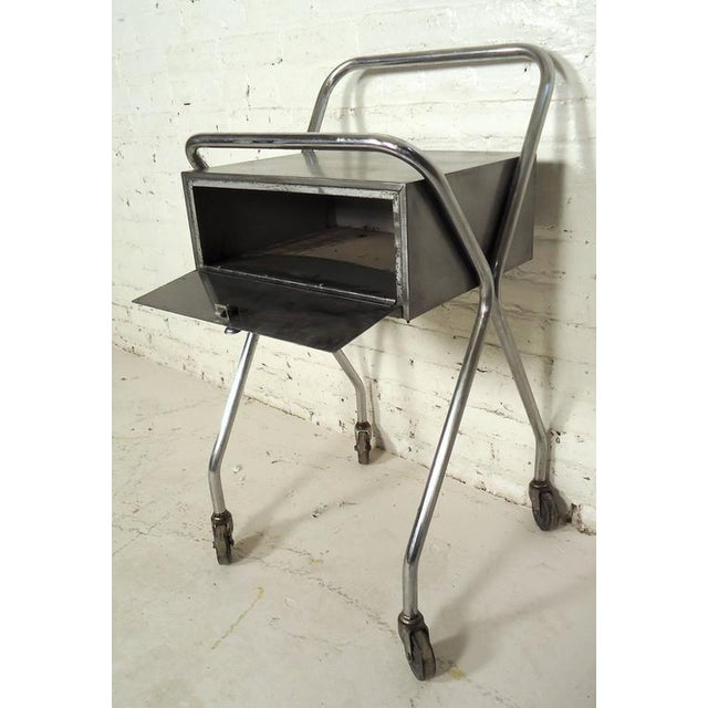Industrial metal rolling table featuring one drawer and a bent chrome frame on wheels. Please confirm item location NY or...