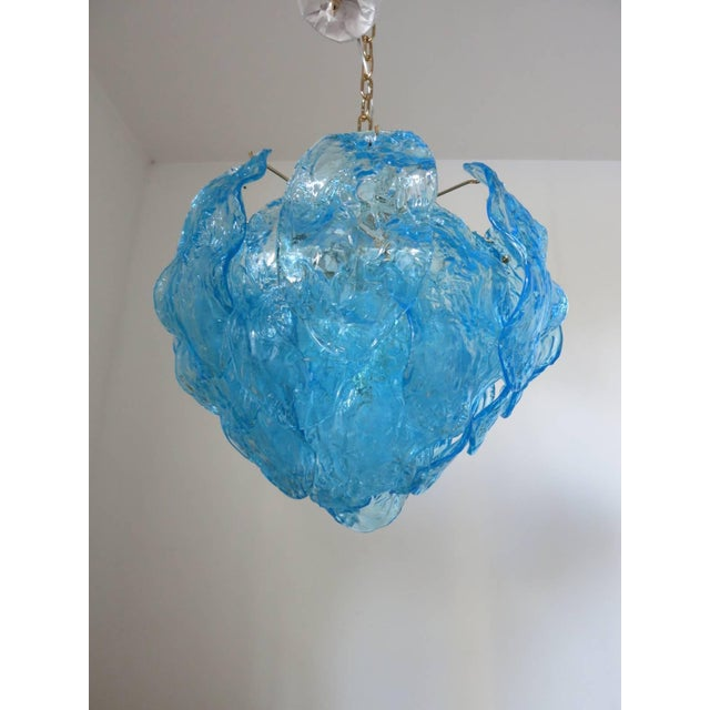 Italian vintage chandelier with hand blown aqua blue Murano glass leaves, mounted on a brass frame / Designed by Mazzega...
