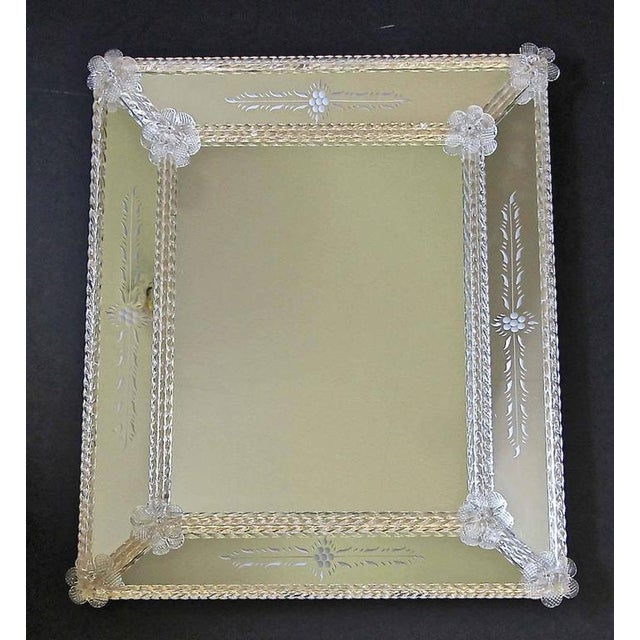 Italian Venetian mirrored glass wall mirror with reversed etched panels, glass flowers and finely twisted glass rods over...