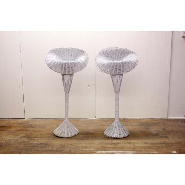 A pair of two tall wicker planter stands styled to look like calla lilies or trumpet flowers. Each stand has a metal...