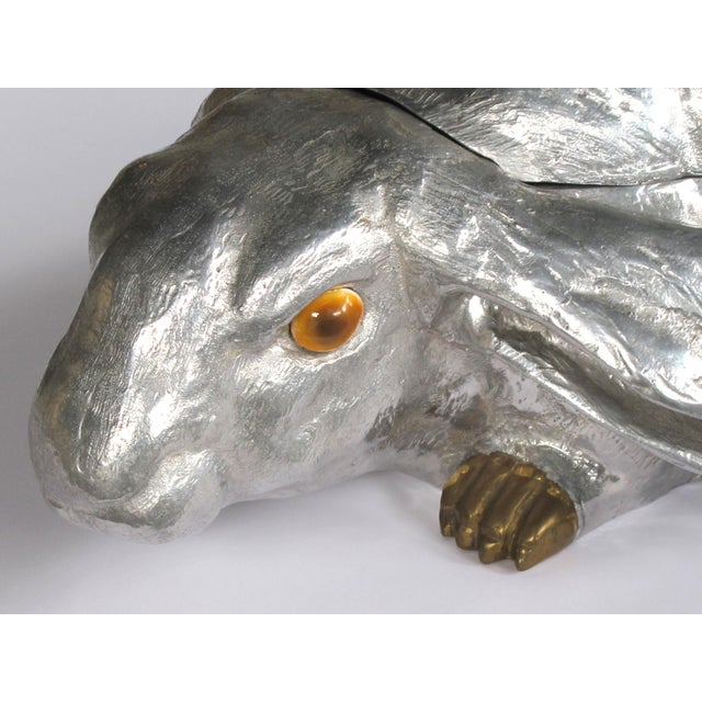 A life-sized rabbit made of polished aluminum with brass feet and carnelian stone eyes; the top half is a hinged lid;...