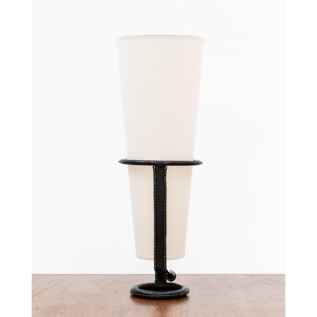 A handsome table lamp by Jacques Adnet in stitched black leather with linen shade. With original toggle cord switch....