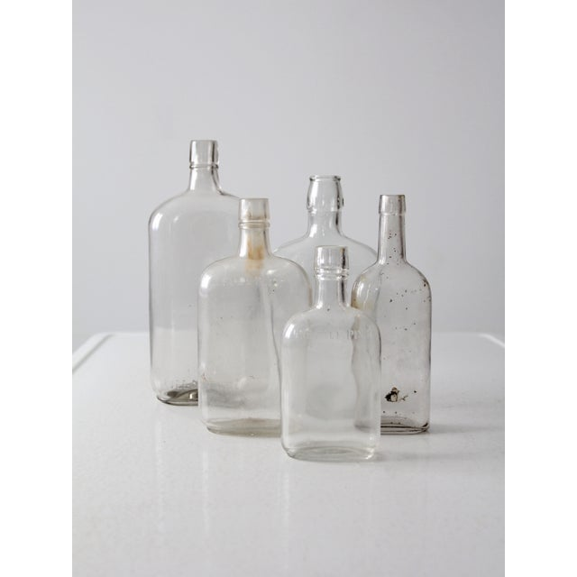 A collection of five antique apothecary bottles. The clear glass bottles feature beautiful patina and markings. The set of...